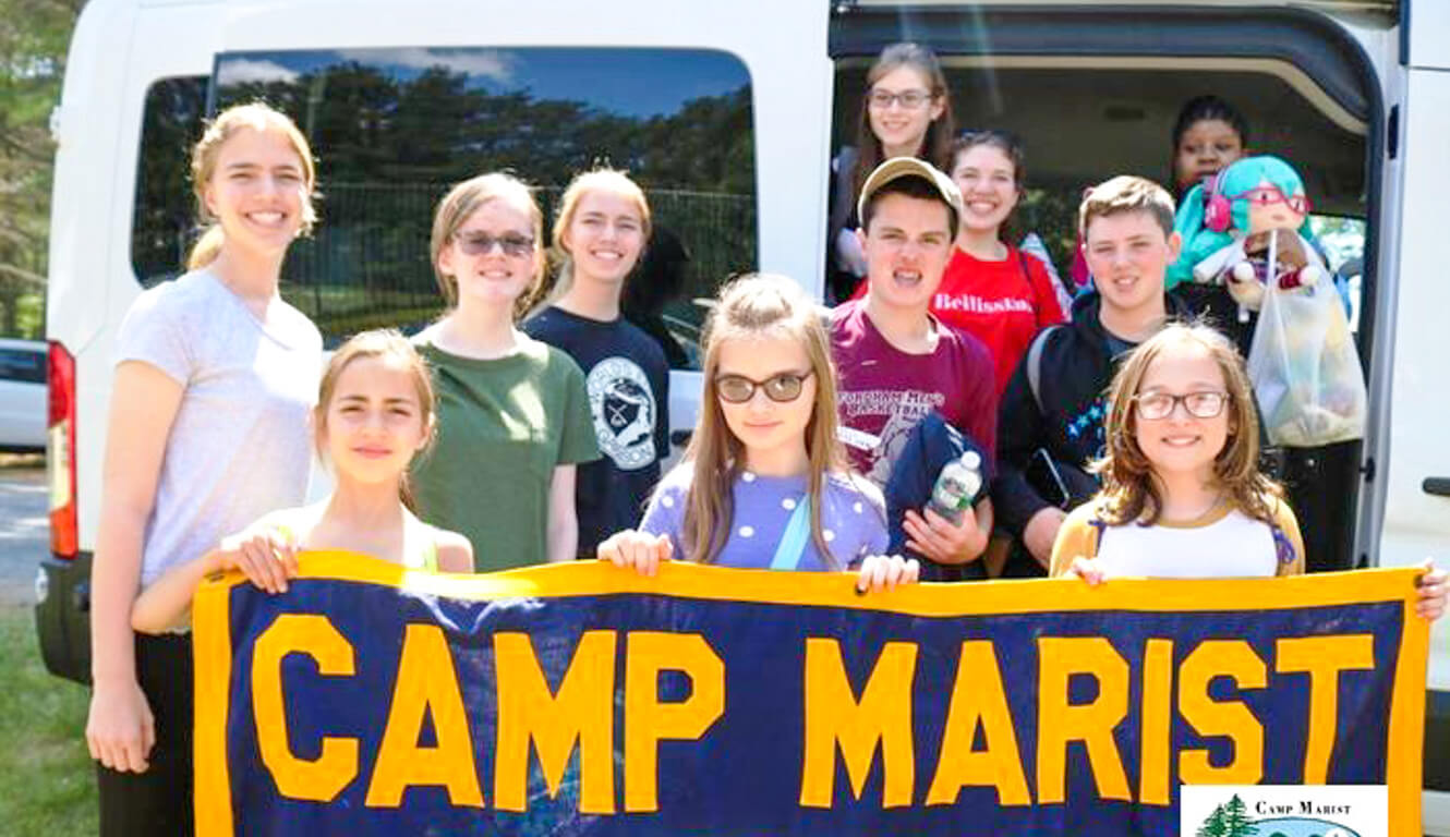 Group of campers hold up Camp Marist banner