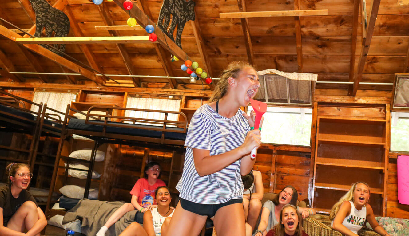 Girl sings into spatula in camp cabin