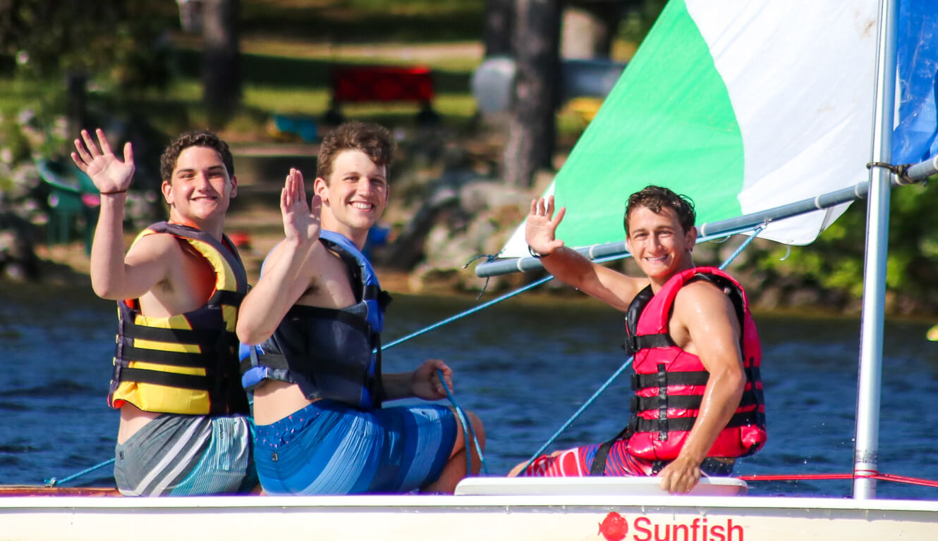 Three campers wave from sailboat